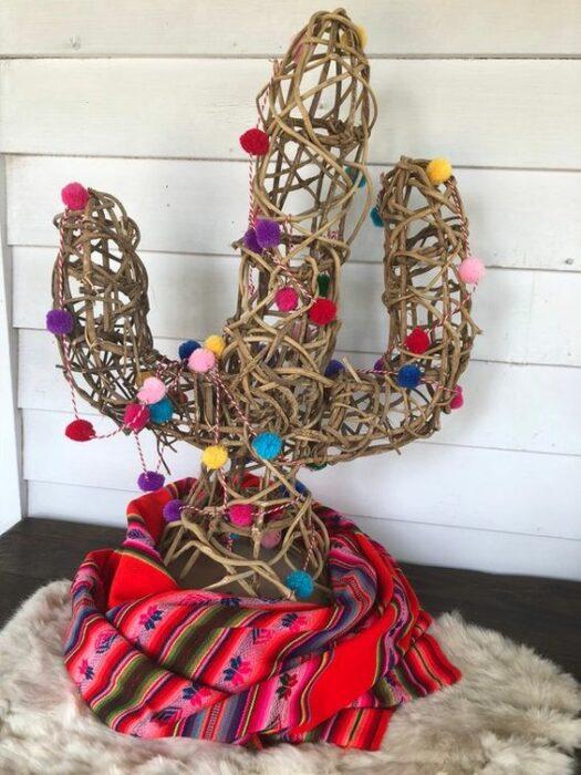 Árbol de navidad en forma de cactus hecho con material de madera y decorado con bolitas de algodón de colores
