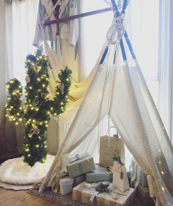 Árbol de navidad en forma de cactus con luces amarillas decorando una habitación con paredes y cortinas blancas cerca de un tepee blanco