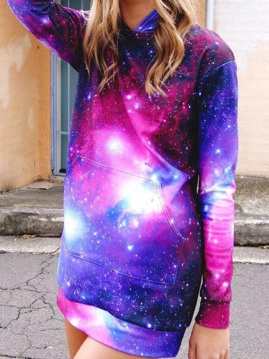 Chica rubia con cabello suelto ondulado con sudadera larga con estampado de galaxia