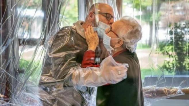 Anciana abraza a su hijo mediante plástico de seguridad en sala de abrazos