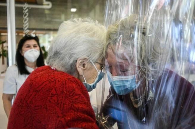 Anciana abraza a su hija por medio de plástico se seguridad en asilo