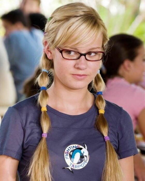 Brie Larson adolescente con blusa azul, dos colitas con ligas de colores y gafas