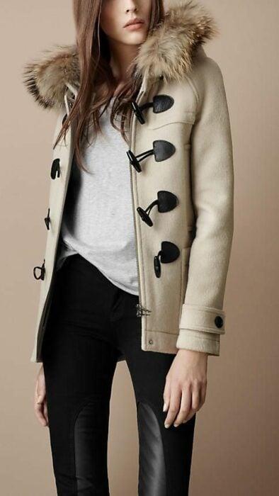 Chica usando chaqueta de color beige con botones de color café oscuro, con blusa blanca y leggings  negros de vinipiel