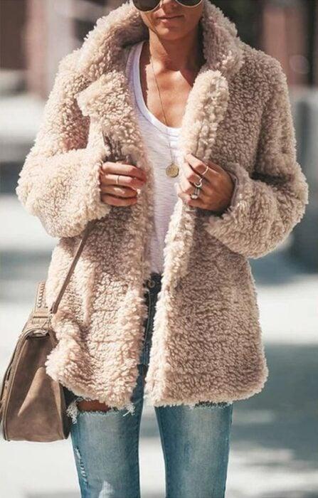 Chica usando chaqueta furry de color arena con blusa blanca, jeans y bolsa de mano
