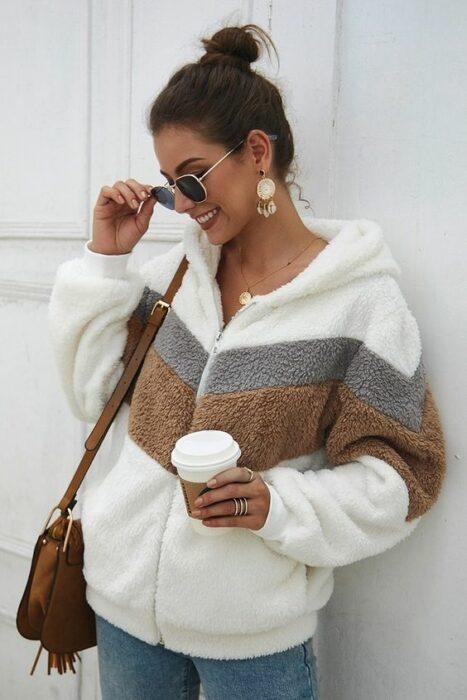 Chaqueta de cierre de color blanco con franja café y gris, con jeans y bolsa de mano color camel