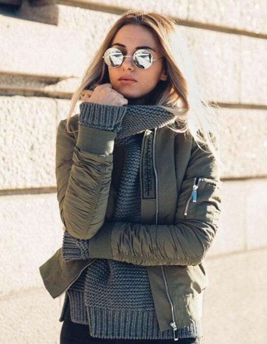 Chica usando caqueta bomber color verde militar con suéter gris debajo y lentes de sol