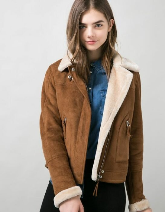 Girl wearing camel-colored jacket with stuffed animal inside and blue blouse and black jeans