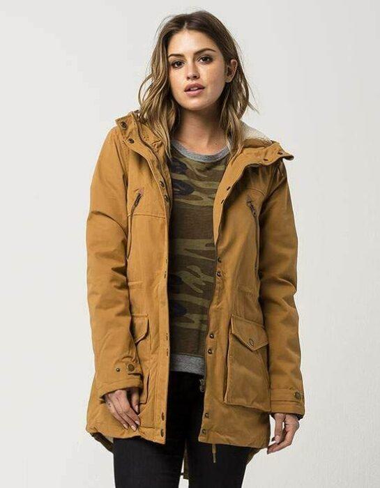 Chica usando chamarra cazadora color mostaza con suéter debajo y jeans oscuros