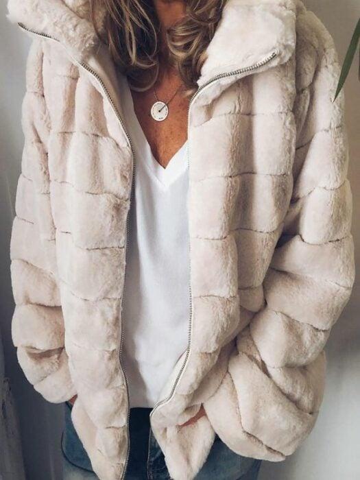 Chica usando chaqueta de pelito color beige con blusa blanca y jeans