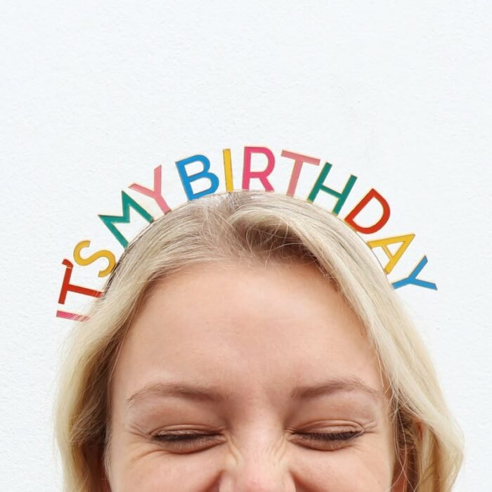 Blonde girl with loose hair closing her eyes with a colorful headband that says it's my birthday