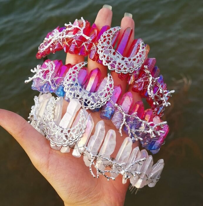 Hand holding three pink and white quartz headbands with a moon in the middle and mermaid-style seaweed with a lake in the background