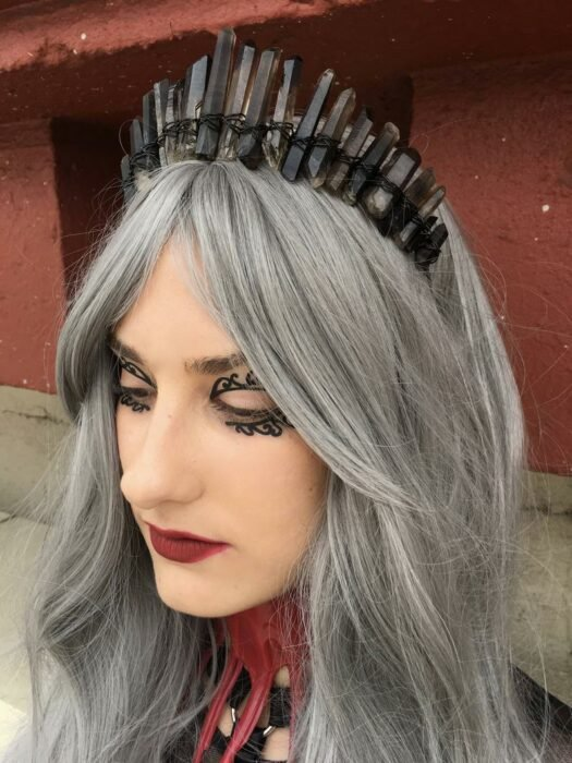White girl with long gray hair with a black crown of quartz