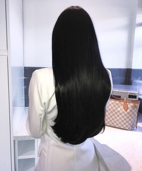 Chica de espaldas con un traje blanco y cabello largo, bonito y negro