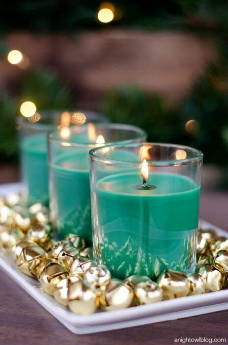 Velas color azul Tiffany en una plato blanco con cascabeles dorados