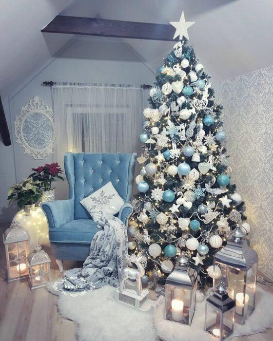 Árbol de navidad verde con esferas turquesas y blancas al lado de un sillón azul en una habitación con muros blancos