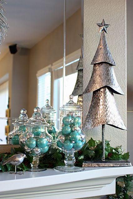 Muebles café con dos jarrones transparentes con esferas turquesas en el interior y un pino de navidad de metal a un lado y detrás un espejo