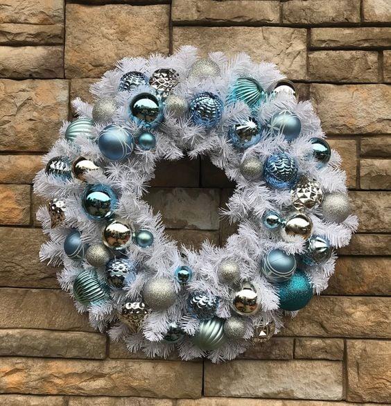 Corona blanca de navidad con esferas azules y plateadas colgada en muro de piedra