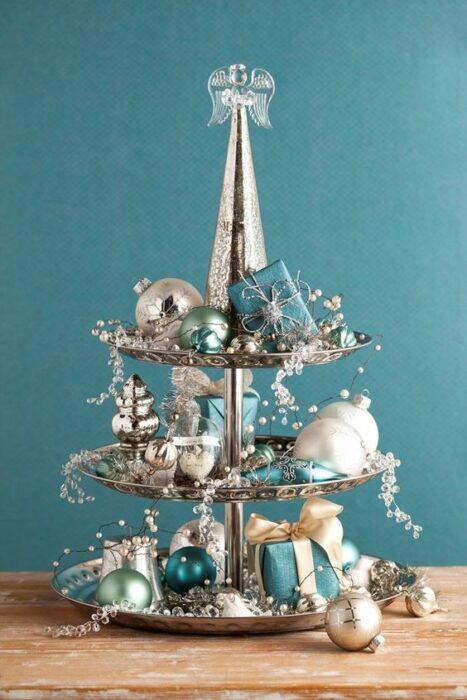 Organizador de joyas plateado con decoración azul turquesa en un mueble café con pared turquesa