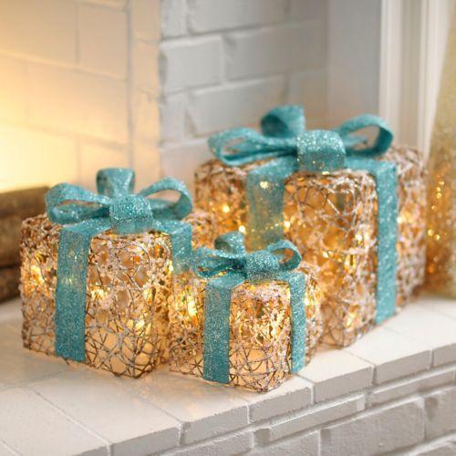 Regalos de decoración con material de estambre con luces navideñas en el interior con un moño turquesa grande encima