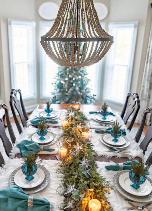 Mesa de comedor con manteles individuales blancos, platos blancos con servilletas turquesas y decoración turquesa  y camino de mesa de ramas de pino