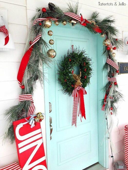 Puerta color azul Tiffany en una casa blanca con de hojas de pino y una corona con un moño rojo