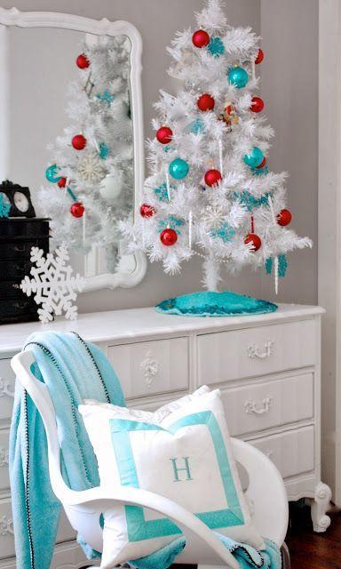 Mueble blanco con un arbolito de navidad blanco con esferas rojas y azul con un espejo detrás
