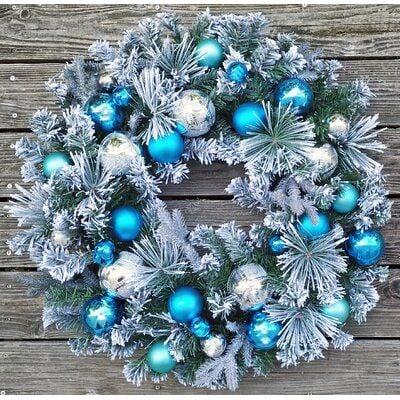 Corona blanca de navidad con esferas azules y plateadas colgada en muro de madera