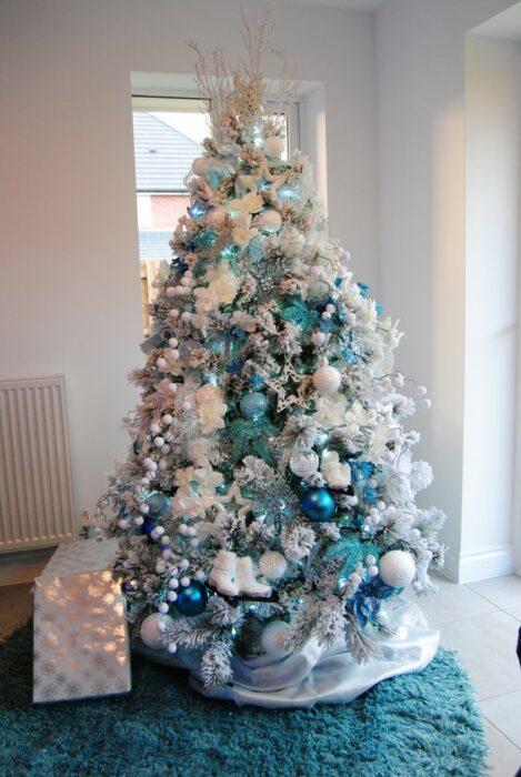 Árbol navideño blanco con esferas azules aqua y turquesa en una habitación blanca