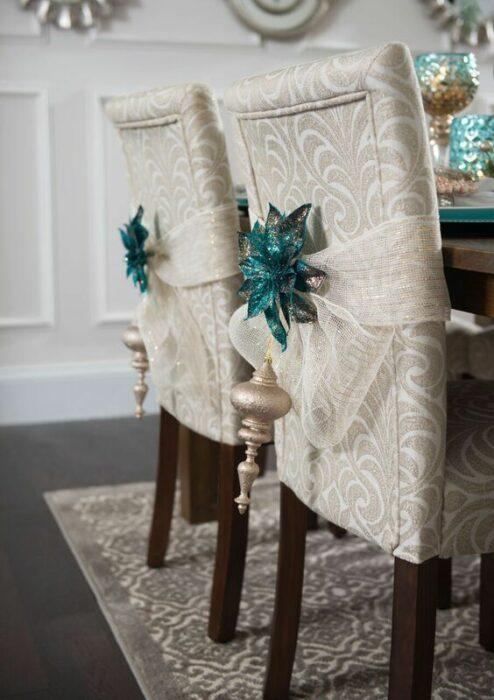Sillas blancas de comer blancas con patas cafés con listón blanco y estrellas azul turquesa en la parte de atrás con una esfera colgante dorada