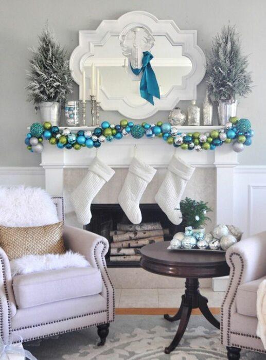 Sala blanca con chimenea con decoración de esferas turquesas, plateadas y verdes con tres botas blancas colgantes