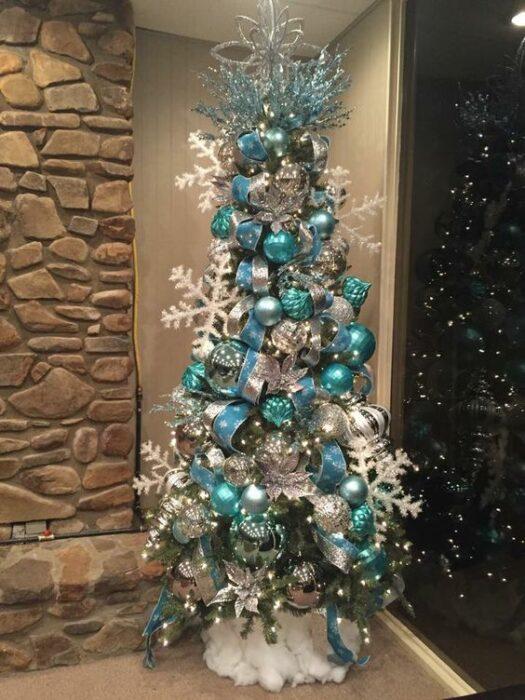 Árbol de navidad blanco con copos grandes blancos y esferas grandes azul Tiffany en una habitación con pared de piedraa en una habitación con pared de piedra
