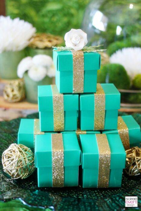 Cajitas de regalos color turquesa con moños dorados con diamantina