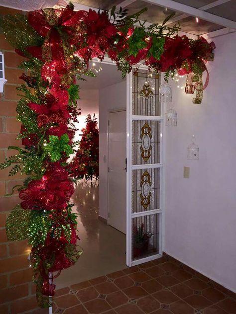Decoración de puerta navideña en colores rojos con verdes, esferas y luces