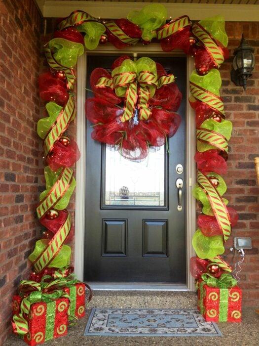 Decoración navideña en una puerta hecha con moños de color rojo con verde