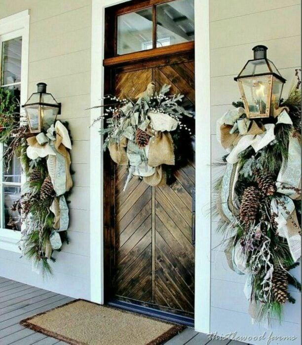 Decoración navideña hecha con piñas, moños y una corona en el centro de la puerta
