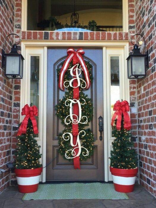Decoración navideña hecha con luces, pinos y moños de color rojo