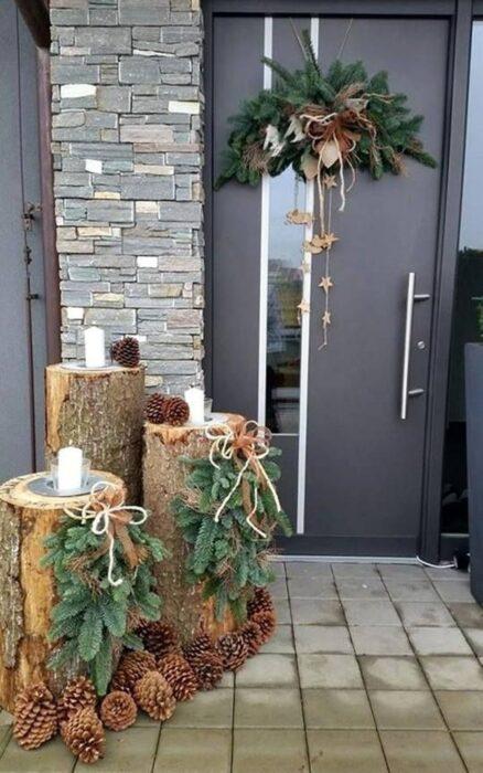Puerta de una casa decorada con troncos y velas y una corona en la puerta