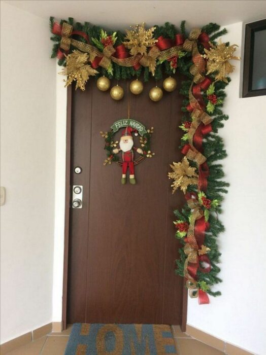 Decoración navideña en una puerta hecha con guirnaldas en colro café con verde y esferas rojas