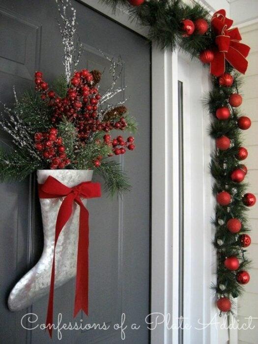Decoración navideña en una puerta hecha con guia de color verde, esferas rojas y una bota plateada