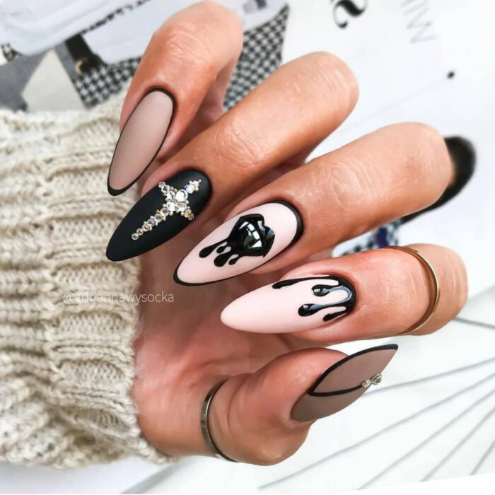 Uñas largas stiletto color rosa, negro y nude, con diseño de curz de pedrería, labios góticos con colmillos de vampiro