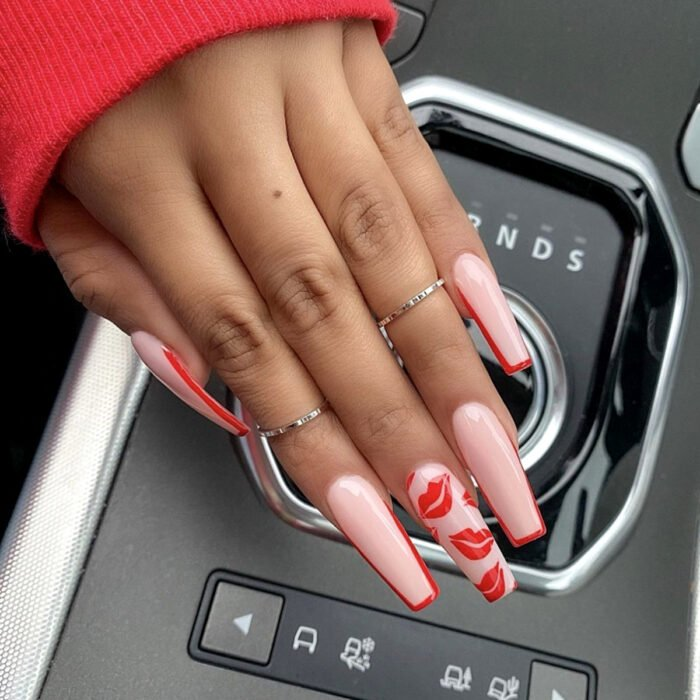 Woman's hands with long square ballerina nails, painted with nude polish, pink, with French manicure design and red planted kisses