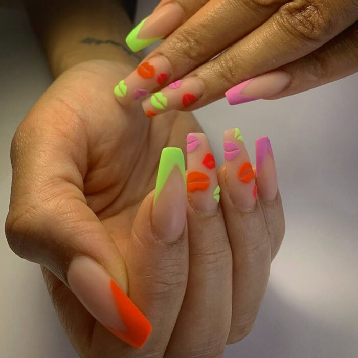 Woman's hands with long square, ballerina nails, painted with matte nude nail polish and neon, green, pink, red and orange colors
