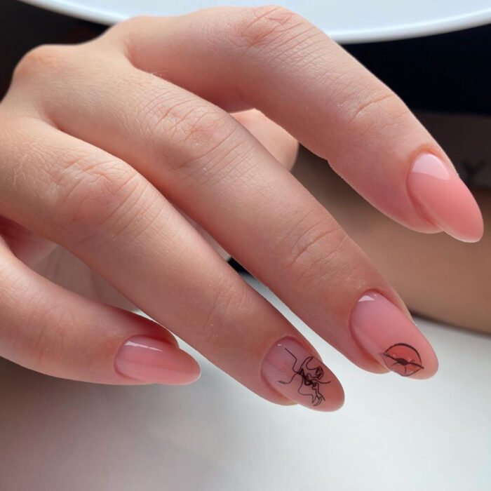 Woman's hands with long almond-shaped nails, painted with nude pink nail polish, with design of lips and people kissing