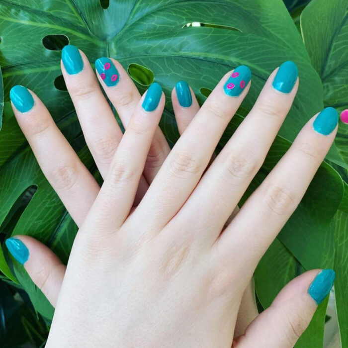 Woman's hands with short round nails, painted with blue polish and with pink lip stickers