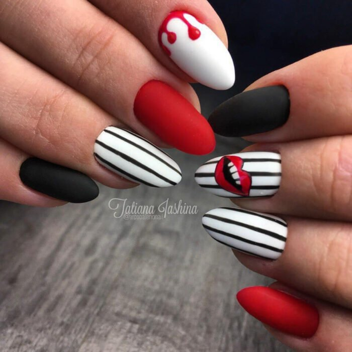 Woman's hands with long almond shaped nails painted with white, red and black matte nail polish with vertical stripe designs and smiling lips
