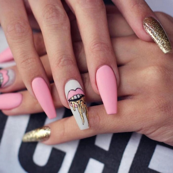 Woman's hands with long square ballerina nails, painted with pink and white matte nail polish, with lip design and pinky with golden glitter