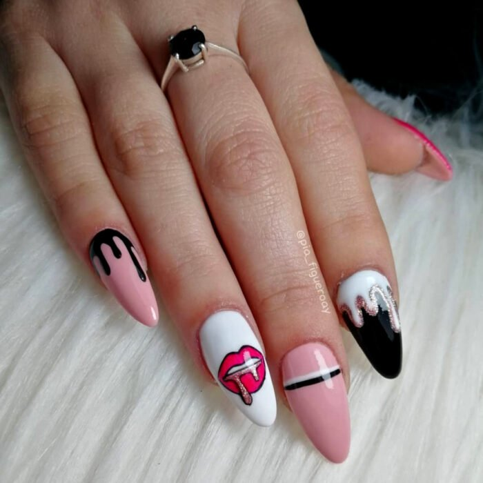 Woman's hands with long stiletto nails painted with baby pink, black and white nail polish with glitter lip design