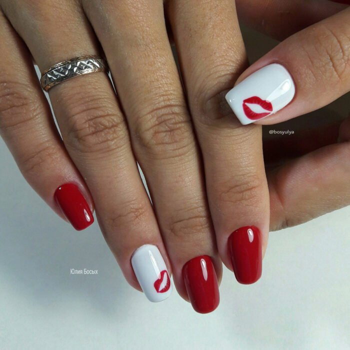 Hands with long square nails painted with red and white polish, with planted kiss design, lips