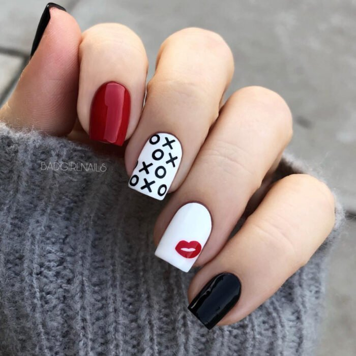 Hands with long square nails painted with red, black and white polish, with planted kiss design, lips and xoxo