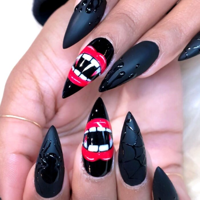 Hands with long stiletto nails painted with matte black polish, with spider, cobweb design and red lips with vampire fangs